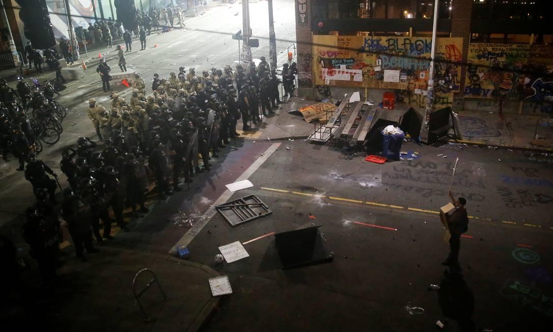 Um manifestante solitário encara policiais perto da Delegacia Leste de Seattle, em Seattle, Washington Foto: LINDSEY WASSON / REUTERS