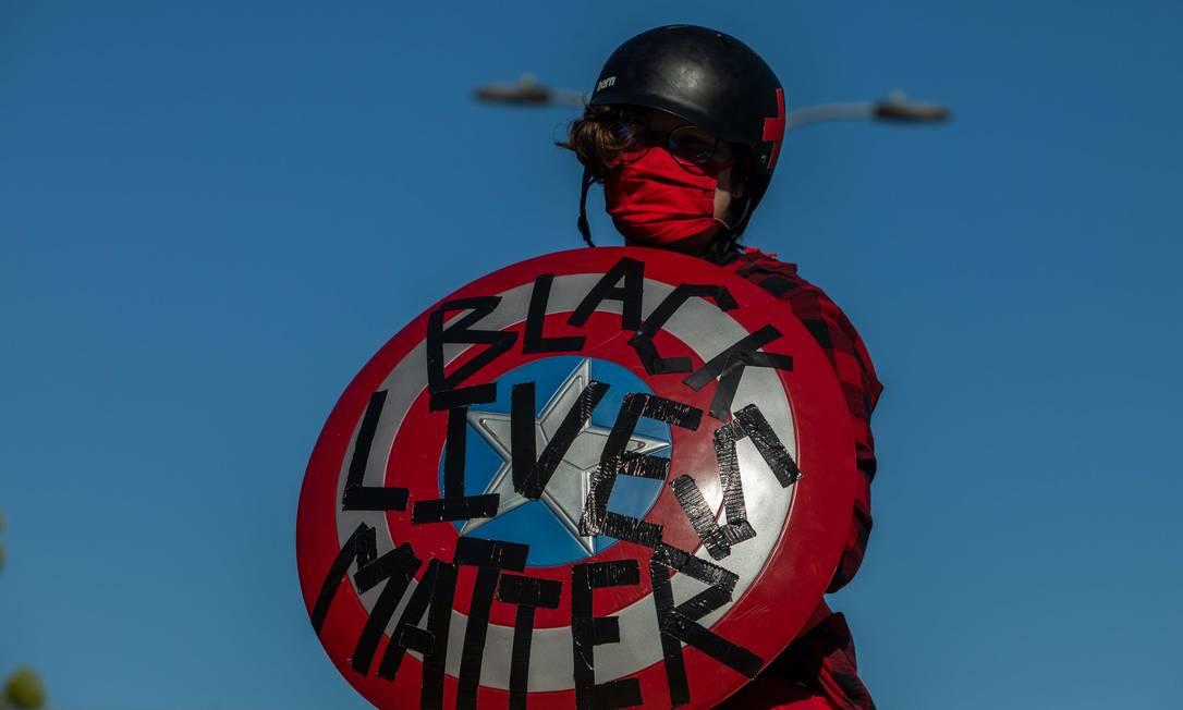 """Manifestante segura escudo do Capitão América, com o lema """"vidas negras importam"""", Los Angeles, Califórnia Foto: Apu Gomes / AFP"""