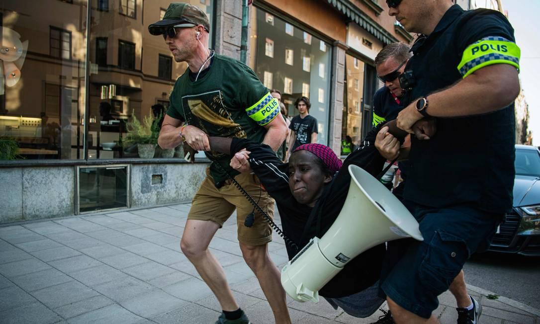 Manifestante negra é arrastada por policiais brancos durante uma manifestação do Black Lives Matter, em Estocolmo, capital da Suécia Foto: JONATHAN NACKSTRAND / AFP