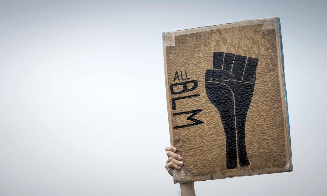 Sigla em inglês para Vidas Negras Importam aparece em cartaz com punho cerrado em protesto, em Deventer, na Holanda Foto: ROBIN VAN LONKHUIJSEN / AFP