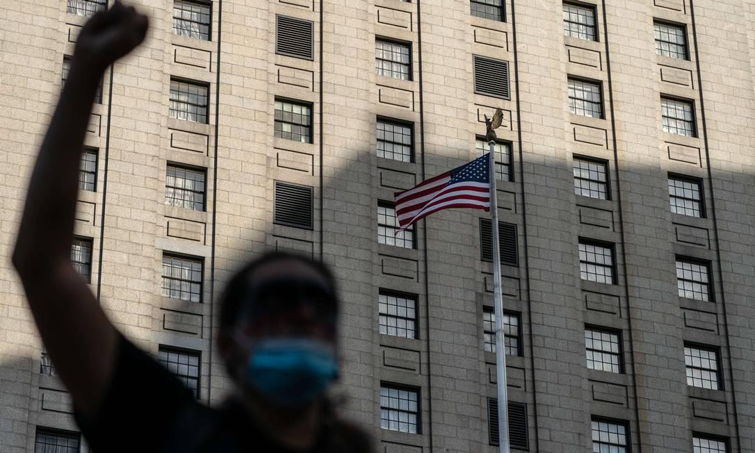 Manifestante levanta o punho enquanto a bandeira americana voa ao fundo durante um protesto de Black Lives Matter, em Nova Iorque Foto: Jeenah Moon / AFP