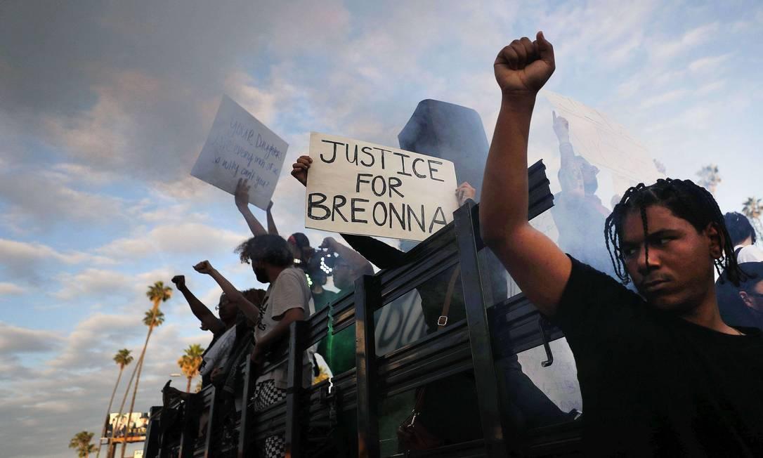 Manifestantes andam a bordo de um veículo com uma máquina de fumaça, com uma placa que lê 'Justiça para Breonna', durante uma manifestação pacífica contra o racismo e a brutalidade policial no Hollywood Boulevard, em Los Angeles, Califórnia. Breonna Taylor foi uma negra, técnica de emergência, de 26 anos, assassinada a tiros, em casa, por policiais do Departamento de Polícia de Louisville Metro, em março Foto: MARIO TAMA / AFP
