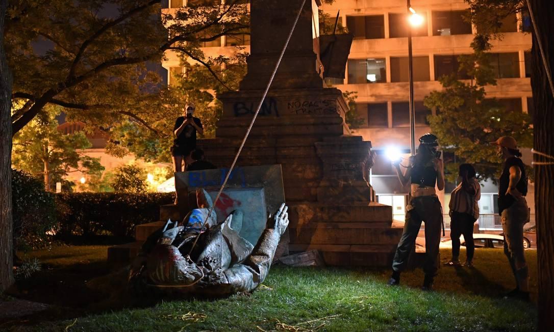 """A estátua do general Albert Pike foi derrubada por manifestantes, na praça do Judiciário, em Wahsington. O protesto desagradou o presidente Donald Trump que twittou que a polícia de Washington """"DC não está fazendo seu trabalho enquanto assiste a uma estátua ser queimada. Essas pessoas devem ser imediatamente presas. Uma desgraça para o nosso país!"""" Foto: ERIC BARADAT / AFP"""