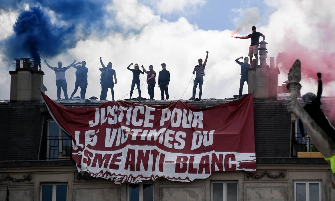 Membros do grupo de extrema-direita Generation Identitaire (GI) penduram faixa onde está escrito 'justiça pelas vítimas do racismo anti-branco', durante um protesto do 'Black Lives Matter' contra o racismo e a polícia brutalidade, na Praça da Republica, em Paris, França Foto: ANNE-CHRISTINE POUJOULAT / AFP