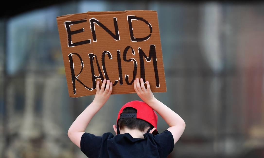 Criança branca segura cartaz pedindo o fim do racismo em ato, no Brooklyn, em Nova Iorque Foto: ANGELA WEISS / AFP
