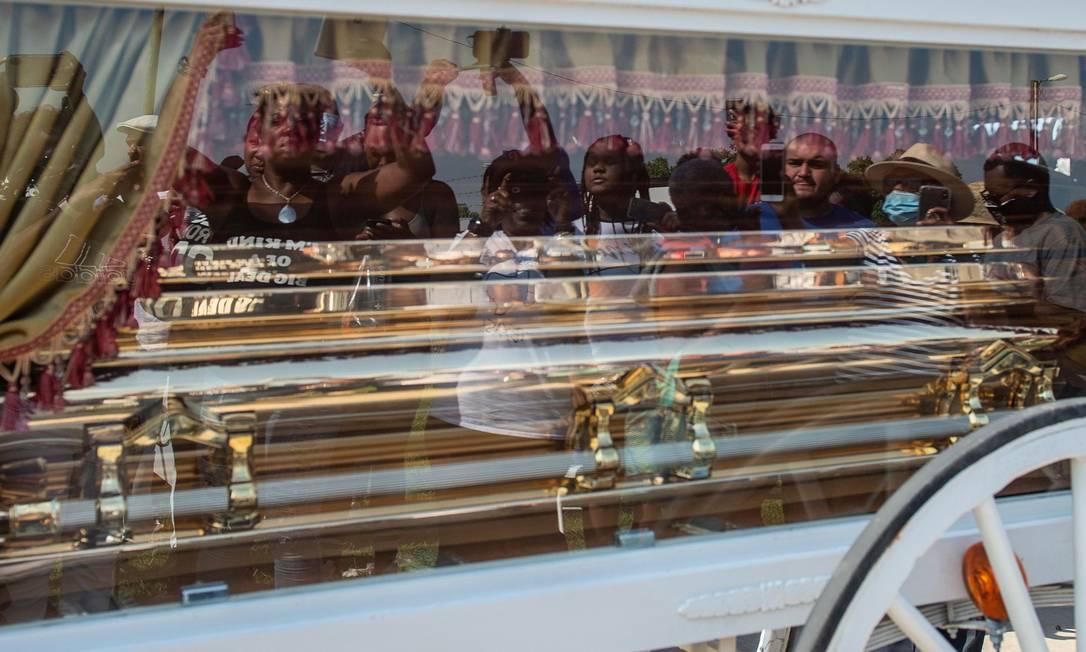 Enlutados são refletidos no caixão de George Floyd, transportado por uma carruagem, para seu local de descanso final, no cemitério de Houston Memorial Gardens em Pearland, Texas Foto: ANDREW CABALLERO-REYNOLDS / AFP