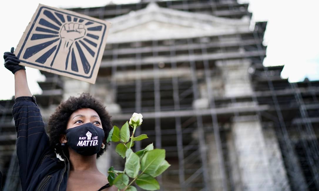 mulher usa máscara protetora na qual está escrita 'Black Lives Matter' e segura uma rosa branca e um cartaz com um punho, durante um protesto anti-racismo, em Bruxelas, Bélgica Foto: KENZO TRIBOUILLARD / AFP