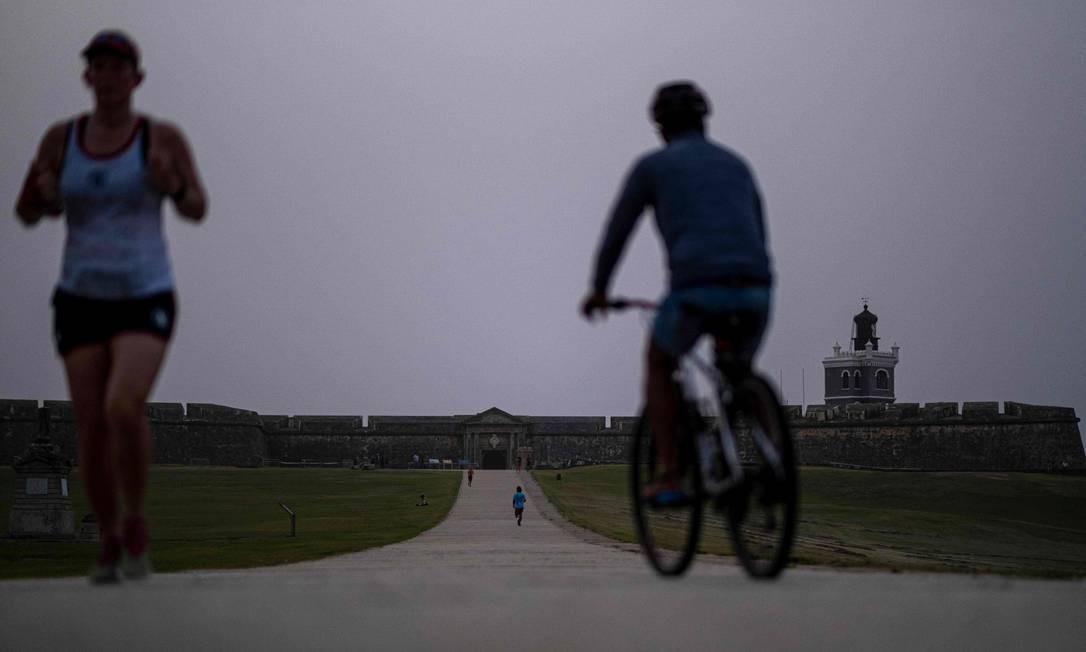 Pessoas exercitam em frente ao Forte El Morro, enquanto o céu é tomado por densa névoa marrom leitosa. Especialistas alertam que fenômeno compromete a qualidade do ar e pode causar danos à saúde Foto: RICARDO ARDUENGO / AFP