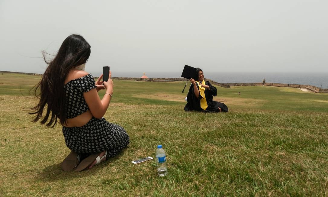 Shakira Maldonado, 23 anos, fotografa sua colega de classe Angeliveth Rodriguez, 22, que se formou em Serviço Social na Universidade Interamericana, em San Juan, Porto Rico. O céu nebuloso ficará marcado na vida da formanda. Segundo metereologistas, a poeira é a mais densa já registrada em meio século Foto: GABRIELLA N. BAEZ / REUTERS
