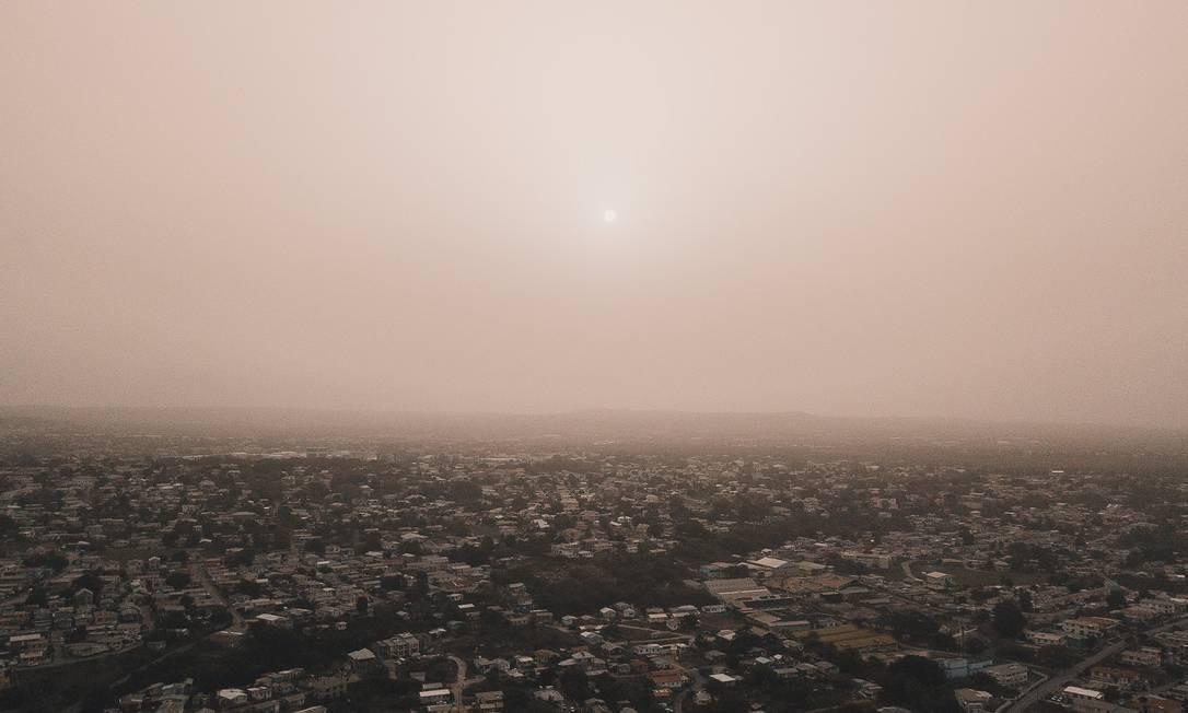 O sol aparece quase imperceptível com o céu tomado pela poeira do Saara, na cidade de Bridgetown, Barbados Foto: Alexander James / Alexander James VIA REUTERS