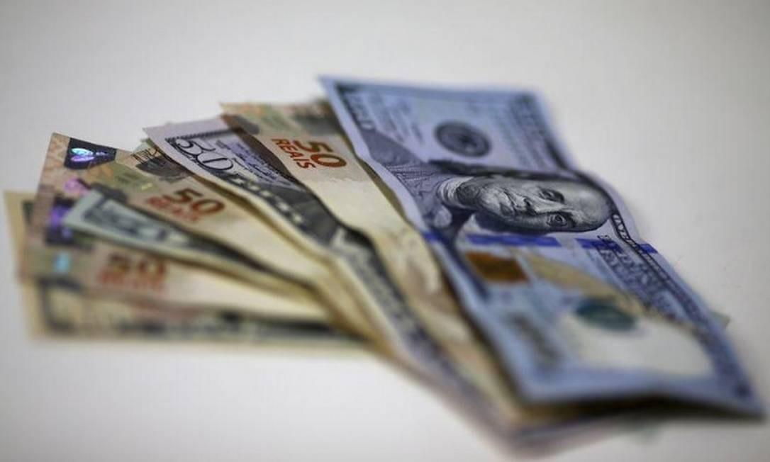 Notas do dólar e do real são dispostas em corretora de câmbio Foto: Reuters