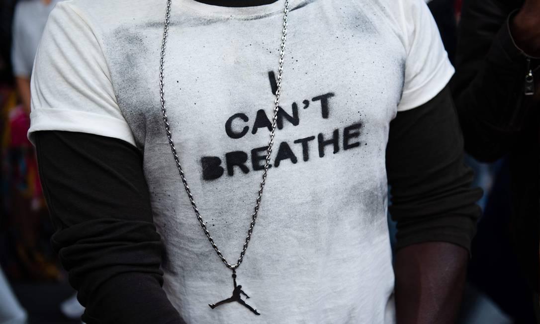 """Manifestante veste blusa estampada com a frase em inglês """"eu não consigo respirar"""", dita por George Floyd antes de morrer sufocado por um policial em 25 de maio Foto: CLEMENT MAHOUDEAU / AFP/13-06-2020"""