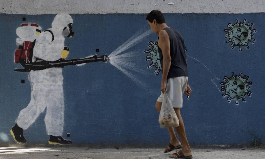 Homem caminha sem máscara em frente a grafite no Bairro do Estácio, Zona Norte do Rio de Janeiro Foto: Luiza Moraes / Agência O Globo