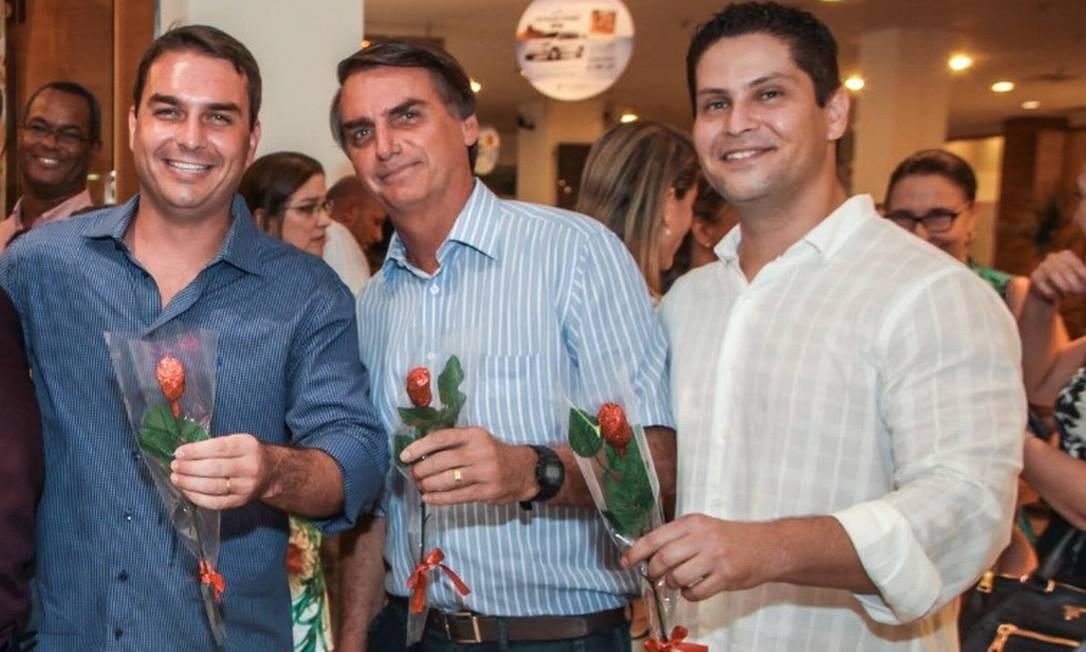O senador Flávio Bolsonaro durante inauguração de sua loja de chocolates, em shopping do Rio, ao lado do pai Jair Bolsonaro e o sócio Alexandre Santini Foto: Reprodução/Facebook