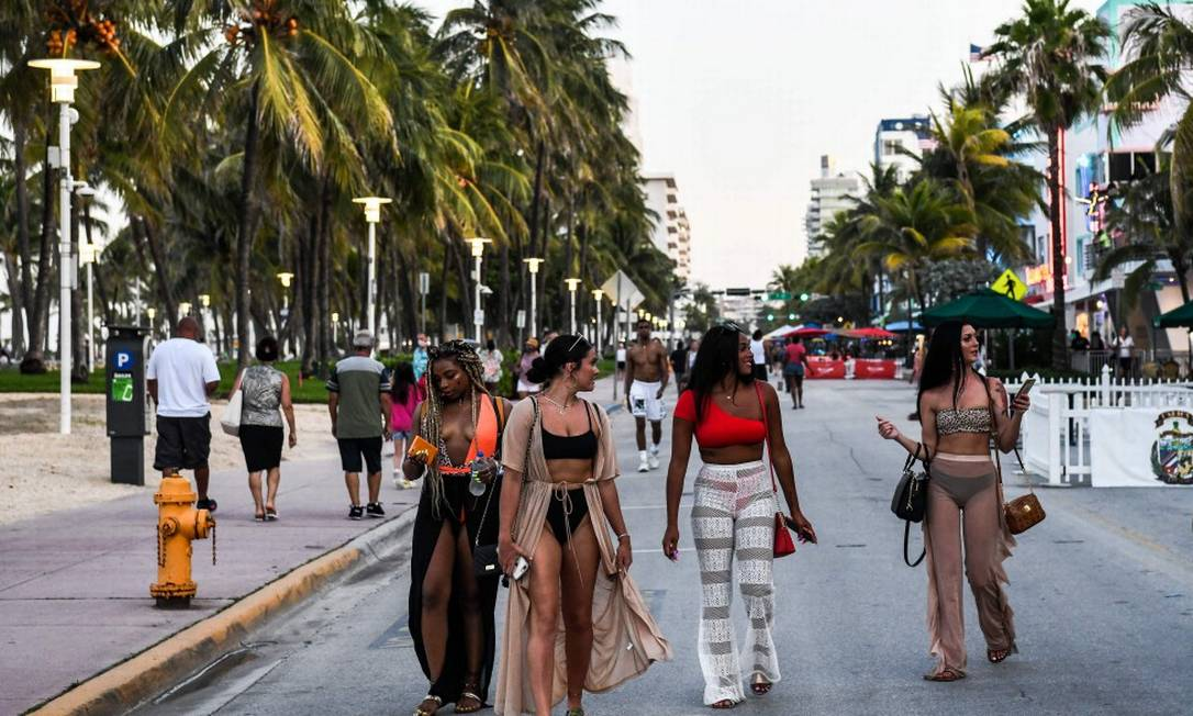 Sem máscaras, mulheres caminham na Ocean Drive, em Miami Foto: CHANDAN KHANNA / AFP / 24-6-2020
