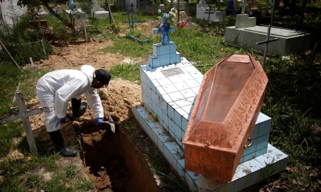 Coveiro com roupas de proteção contra o coronavírus enterra vítima da Covid-19 no cemitério Recanto da Paz, em Breves, na Ilha de Marajó (PA) Foto: UESLEI MARCELINO / REUTERS