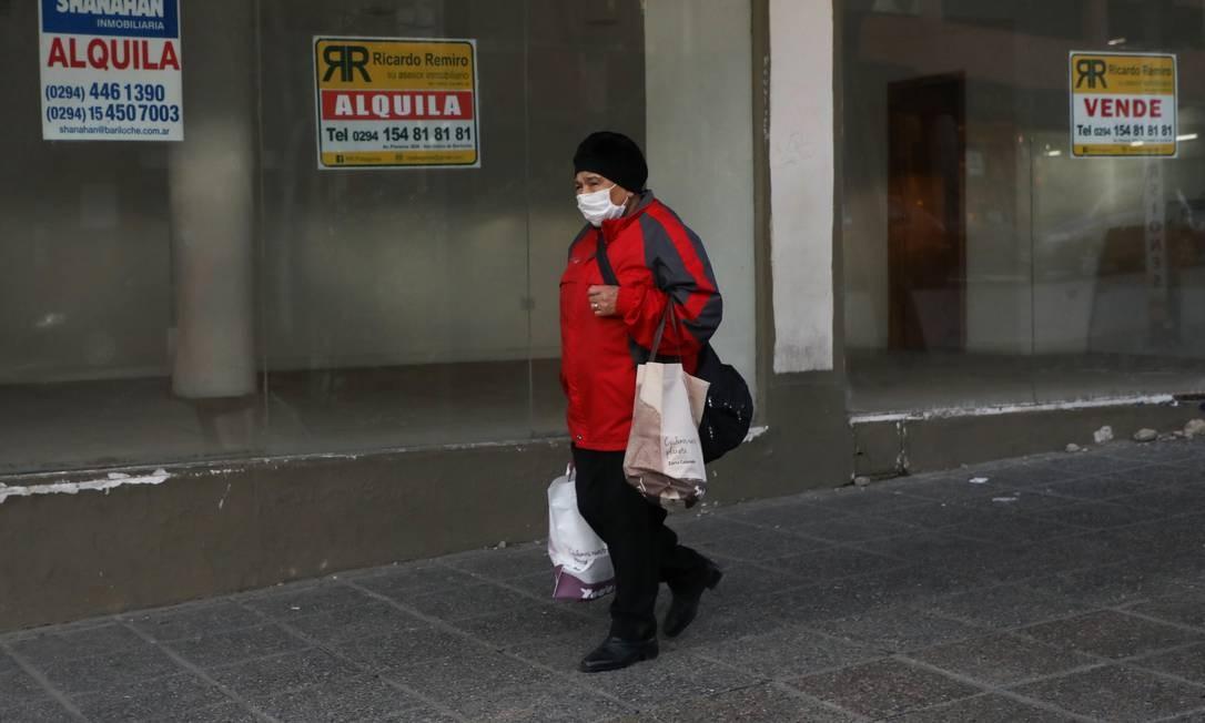 Mulher caminha em frente a lojas com placas de venda e aluguel em Bariloche. Um dos destinos turísticos mais procurados da Argentina sofre as consequências da pandemia Foto: FRANCISCO RAMOS MEJIA / AFP