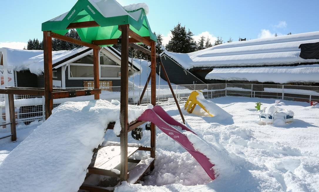 Parque para crianças está cobertos de neves e vazio, sem a presença dos turistas que costumam visitar a região nesta época do ano Foto: FRANCISCO RAMOS MEJIA / AFP