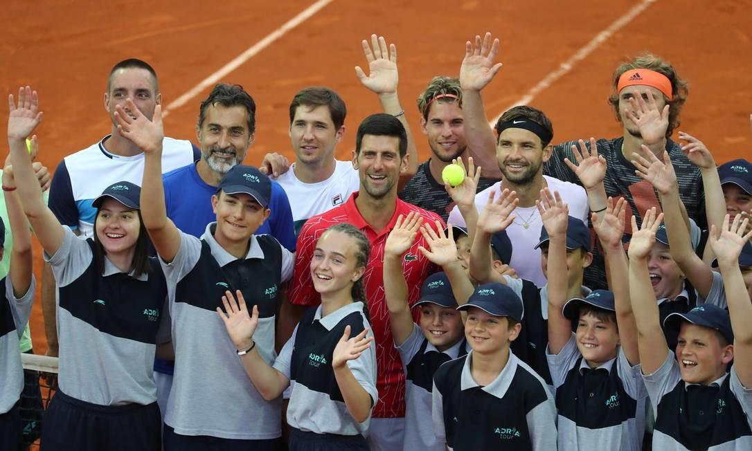 Novak Djokovic cercado de tenistas e boleiros durante torneio de tênis em Belgrado Foto: Marko Djurica / REUTERS