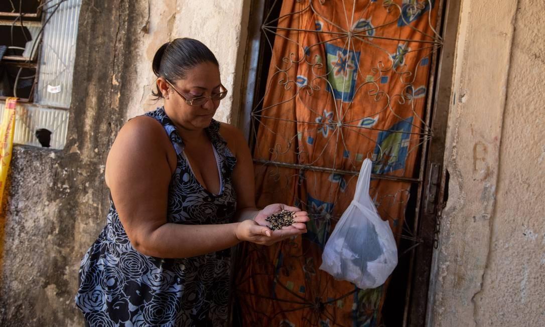 Flávia Jane e o feijão estragado: cesta básica foi entregue pela escola da filha Foto: BRENNO CARVALHO / Agência O Globo