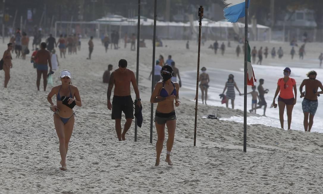 Apesar do tempo nublado, domingo foi de intenso movimento na praia de Copacabana, na areia e no calçadão Foto: FABIANO ROCHA / Agência O Globo
