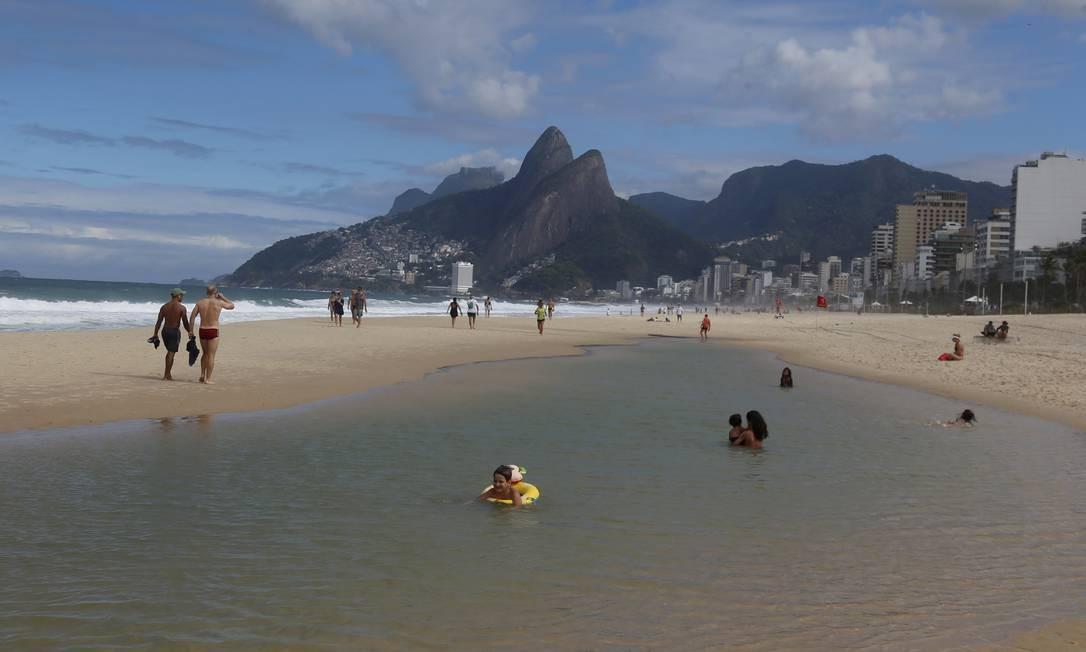 Por conta do mar agitado, uma piscina natural se formou na areia de Ipanema, o que atraiu famílias com crianças Foto: FABIANO ROCHA / Agência O Globo