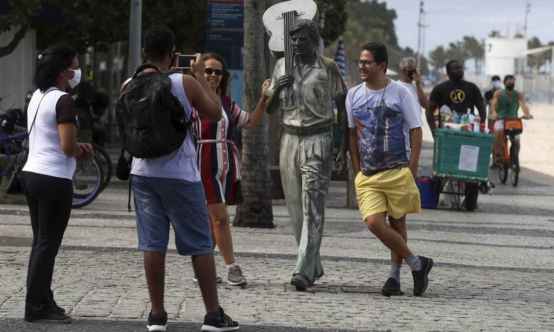 Pessoas tiram fotos ao lado da estátua de Tom Jobim, em Ipanema Foto: FABIANO ROCHA / Agência O Globo