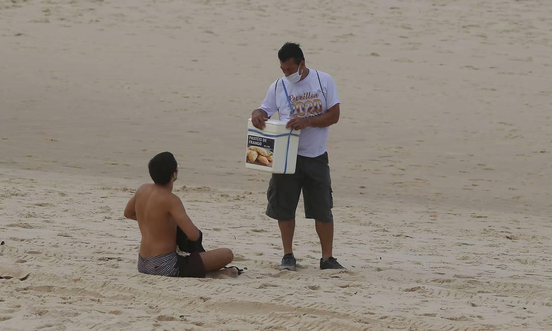 Ambulante oferece pastéis à um banhista na Praia de Ipanema Foto: FABIANO ROCHA / Agência O Globo