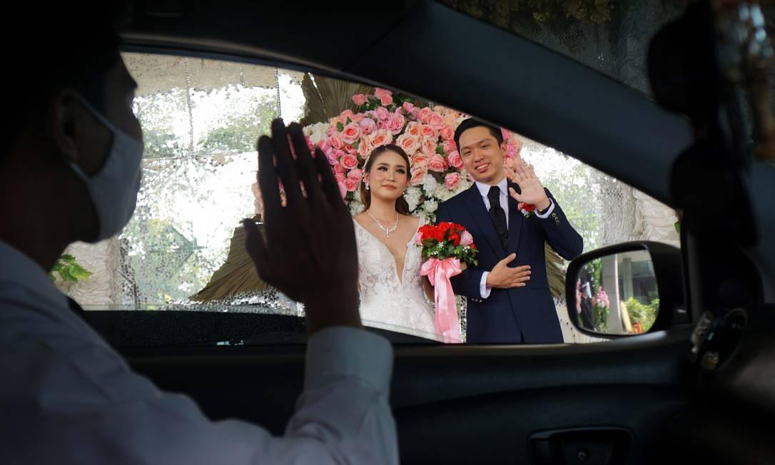 Um convidado dentro de um carro acena para casal de noivos durante cerimônia de casamento que implementa medidas de distanciamento social, em Tangerang, na Indonésia Foto: FAJRIN RAHARJO / AFP