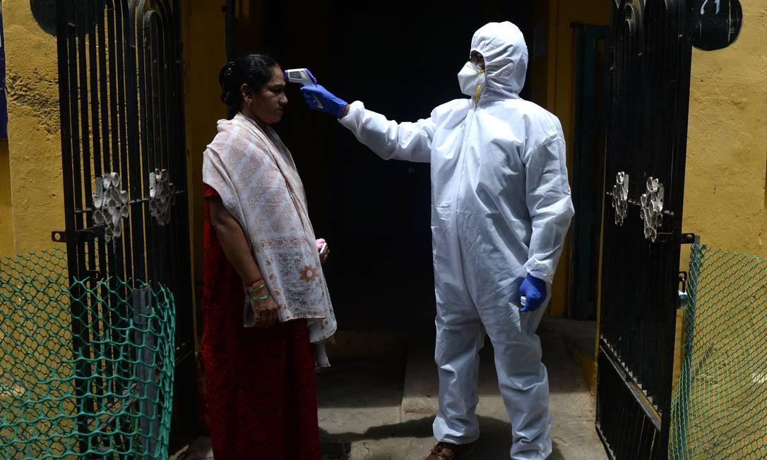 Uma médica verifica a temperatura de uma mulher em sua residência como parte de uma campanha móvel nas zonas de contenção durante um bloqueio de prevenção contra o coronavírus, em Chennai, na Índia Foto: ARUN SANKAR / AFP
