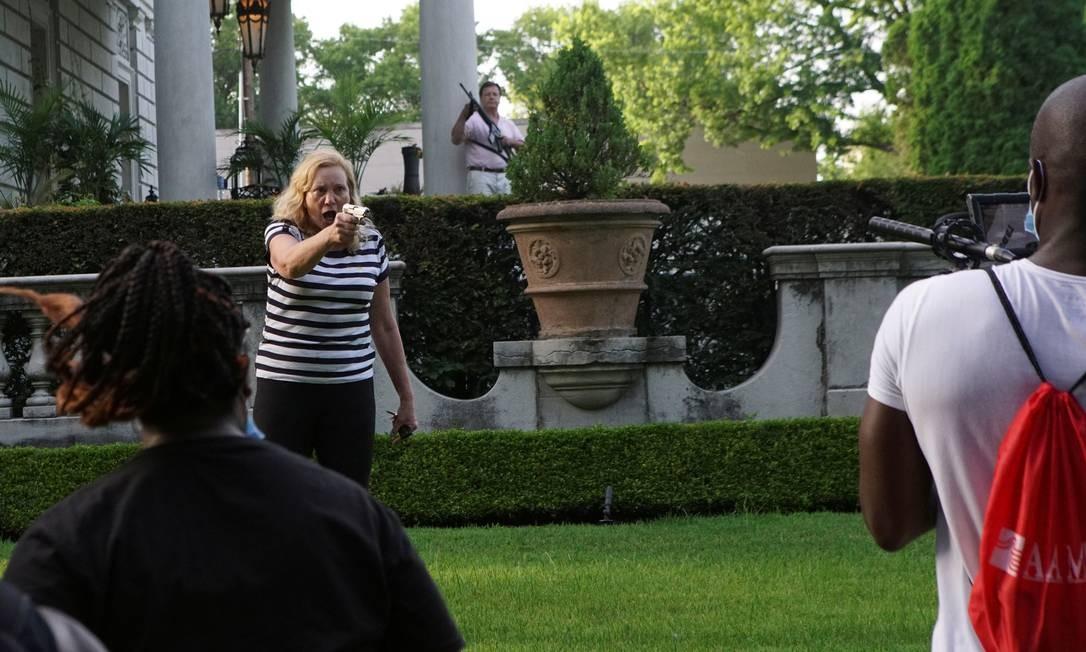 Um casal aponta suas armas de fogo contra manifestantes quando entram em seu bairro durante um protesto contra a prefeita de Saint Louis, Lyda Krewson, em Saint Louis, no estado de Missouri, EUA Foto: LAWRENCE BRYANT / REUTERS
