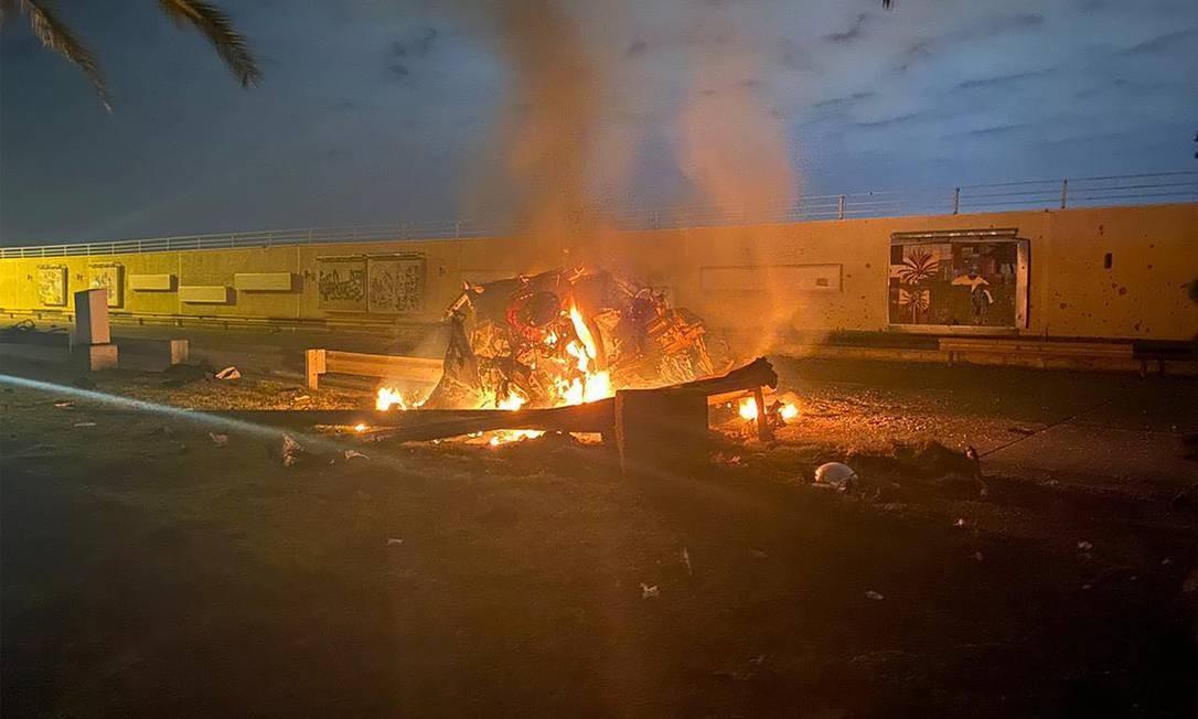 Imagem registrada em janeiro e publicada pelo escritório de mídia das forças de operações conjuntas do exército iraquiano mostra veículo destruído próximo do local onde comboio do general iraniano Qassem Soleimani sofreu um ataque dos EUA, em 3 de janeiro de 2020, na estrada do aeroporto internacional de Bagdá, no Iraque Foto: AFP