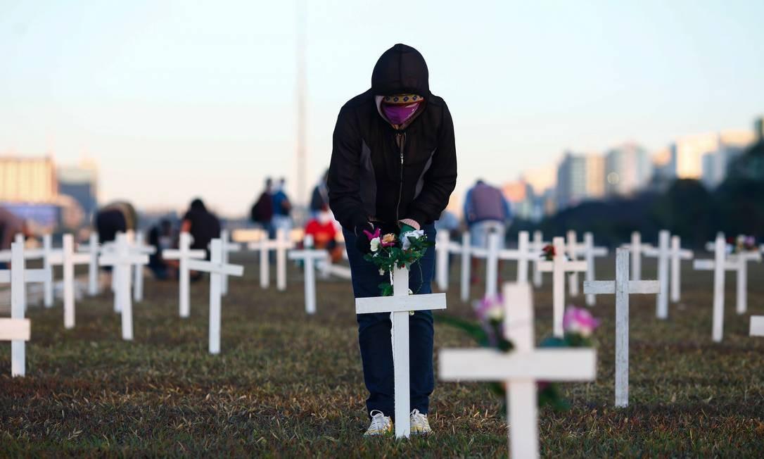 Um manifestante coloca flores em uma cruz durante homenagem às pessoas que morreram de Covid-19, nas quais 1.000 cruzes foram colocadas na frente do Congresso Nacional em Brasília, no domingo. Foto: SERGIO LIMA / AFP