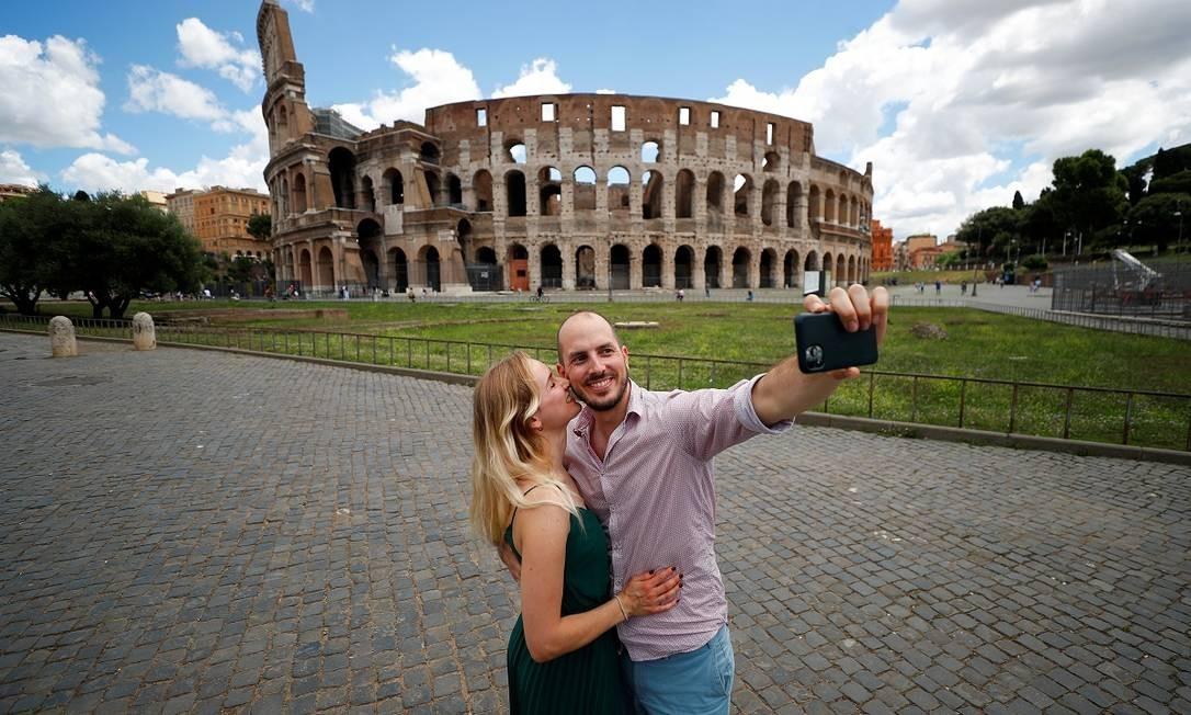 Turistas alemães tiram uma foto em frente ao Coliseu, em Roma, muito vazio Foto: Guglielmo Mangiapane / Reuters