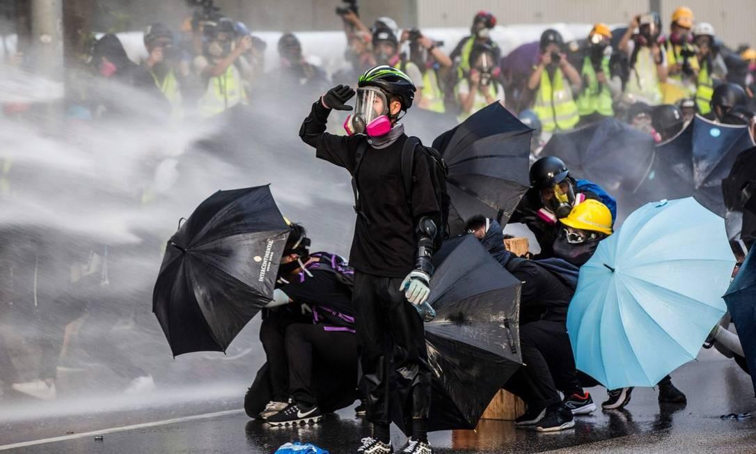 Manifestantes pró-democracia se protegem de jatos d'água da polícia durante protestos no lado de fora da sede do governo de Hong Kong Foto: ISAAC LAWRENCE / AFP