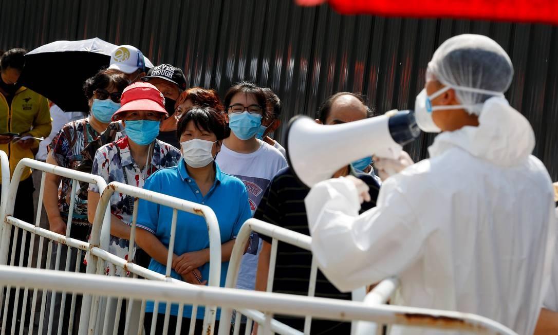 Pessoas fazem fila para receber testes de ácido nucleico em um local de teste temporário após um novo surto da COVID-19 em Pequim, China Foto: THOMAS PETER / REUTERS