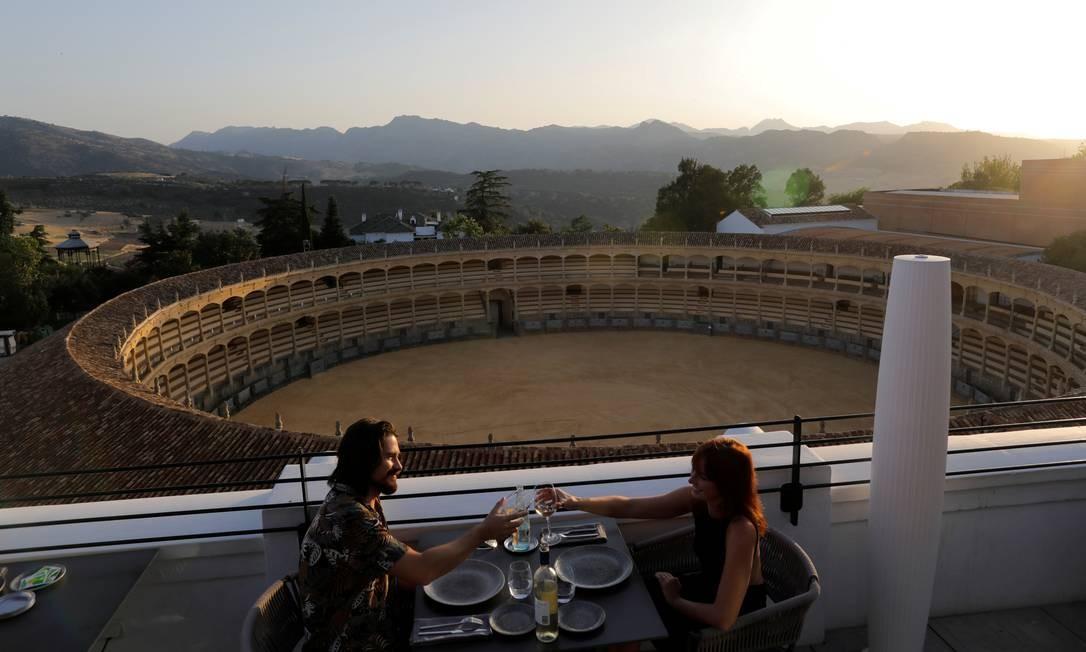Casal de turistas australianos brinda com taças de vinho após um relaxamento das restrições, no restaurante do terraço do hotel Catalonia Ronda, em frente a uma praça de touros, ao pôr do sol no centro de Ronda, sul da Espanha Foto: JON NAZCA / REUTERS