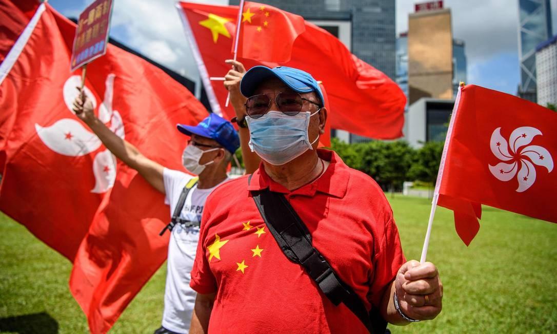 Apoiadores pró-China exibem bandeiras chinesas e de Hong Kong durante uma manifestação perto da sede do governo em Hong Kong, quando a China aprovou uma lei de segurança nacional abrangente para a cidade Foto: ANTHONY WALLACE / AFP