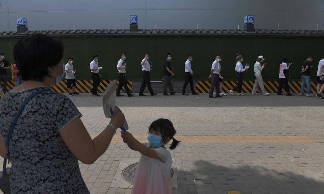 Pessoas esperam na fila para serem submetidas aos testes de cotonetes de coronavírus, em uma estação de testes, em Pequim. A capital da China suspendeu parcialmente um bloqueio de uma semana imposto para impedir uma segunda onda temida de infecções Foto: GREG BAKER / AFP