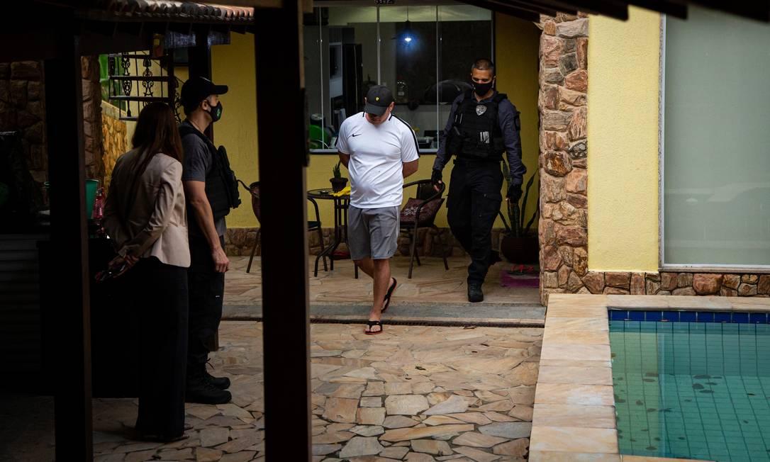 Devidamente vestido, Mag é algemado e levado para a Divisão de Homicídios, na Barra da Tijuca Foto: Hermes de Paula / Agência O Globo