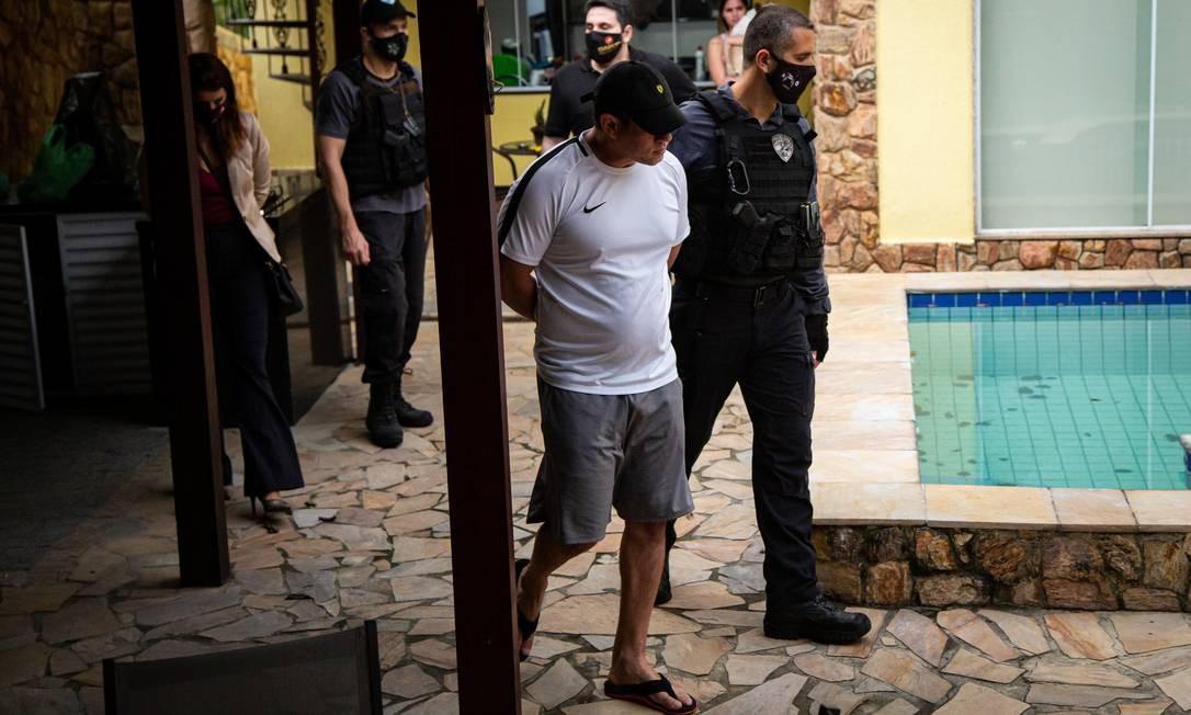 Leonardo Gouvea da Silva , o Mad, é conduzido por um agente logo após ser preso Foto: Hermes de Paula / Agência O Globo