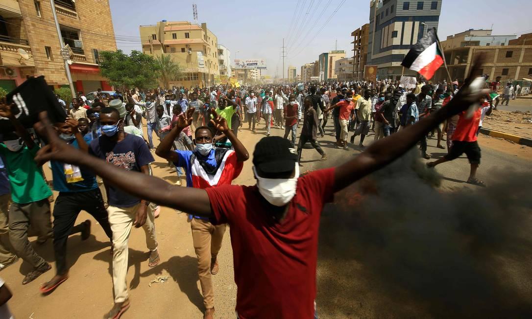 Manifestantes sudaneses gesticulam enquanto a fumaça sobe com a queima de pneus durante um protesto na rua Sixty, no leste da capital Cartum Foto: ASHRAF SHAZLY / AFP