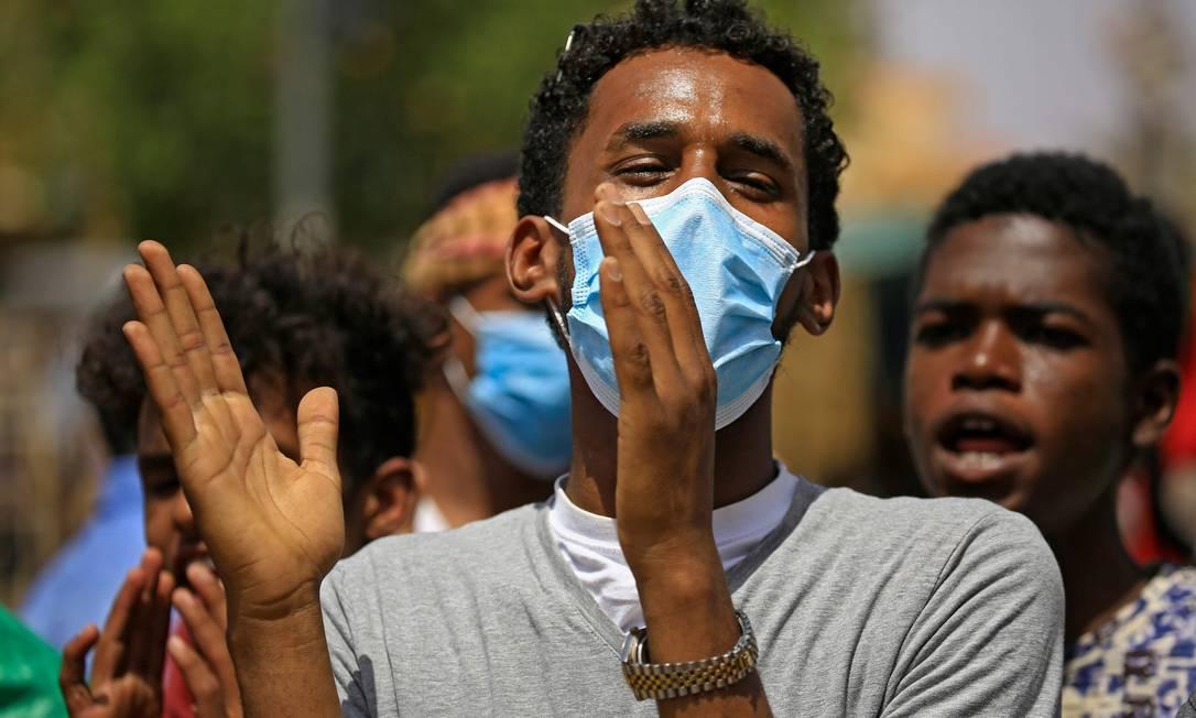 Um manifestante sudanês usando uma máscara protetora em meio às palmas da pandemia do COVID-19 durante um protesto na rua Sixty, no leste da capital Cartum Foto: ASHRAF SHAZLY / AFP