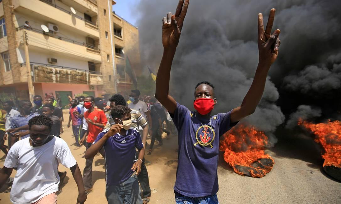 Um manifestante sudanês usando uma máscara protetora faz sinal da vitória enquanto a fumaça sobe dos pneus em chamas durante um protesto na rua Sixty, no leste da capital Cartum Foto: ASHRAF SHAZLY / AFP