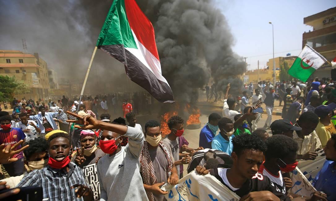Manifestantes sudaneses levantam bandeiras nacionais enquanto a fumaça sobe com a queima de pneus durante um protesto na rua Sixty, no leste da capital Cartum Foto: ASHRAF SHAZLY / AFP