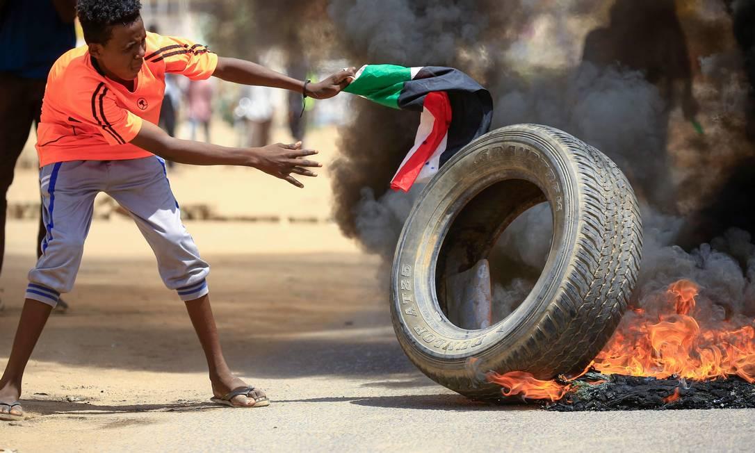 Um manifestante sudanês adiciona um pneu a uma pilha em chamas durante um protesto na rua Sixty, no leste da capital Cartum Foto: ASHRAF SHAZLY / AFP
