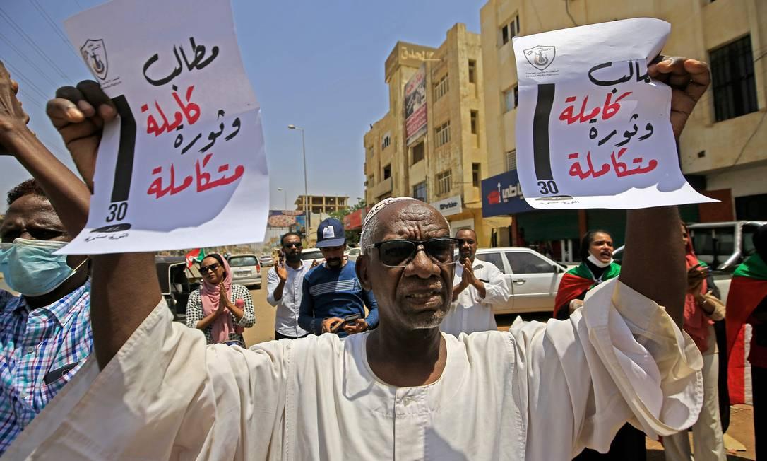 Um manifestante sudanês levanta cartazes exigindo a plena implementação de objetivos revolucionários durante um protesto na rua Sixty, no leste da capital Cartum Foto: ASHRAF SHAZLY / AFP