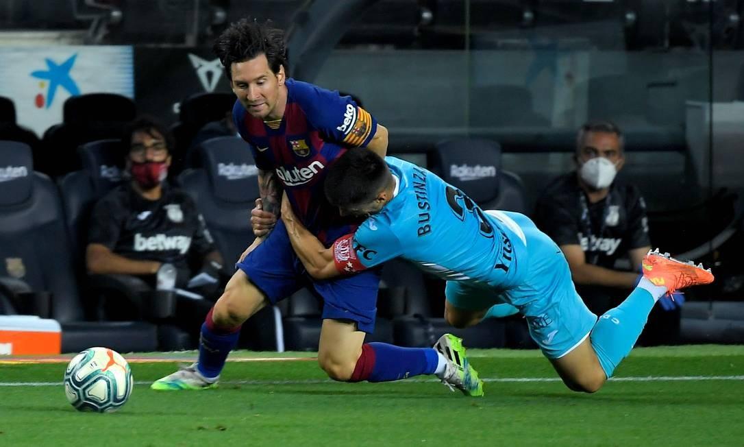 Messi é agarrado pelo zagueiro espanhol Legai, Unai Bustinza, durante o jogo da liga espanhola contra o CD Leganes, no Camp Nou, em Barcelona, em 16 de junho de 2020 Foto: LLUIS GENE / AFP