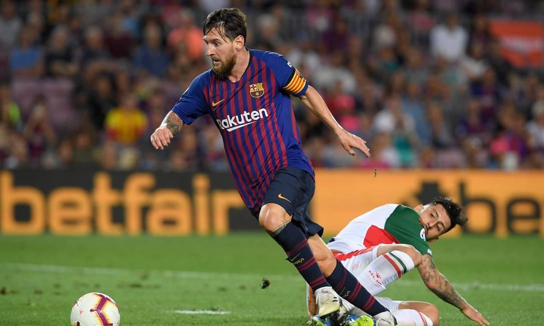 O atacante argentino dribla o zagueiro chileno da Alaves, Guillermo Maripan, durante a partida da liga espanhola, no estádio Camp Nou, em Barcelona, em 18 de agosto de 2018 Foto: LLUIS GENE / AFP