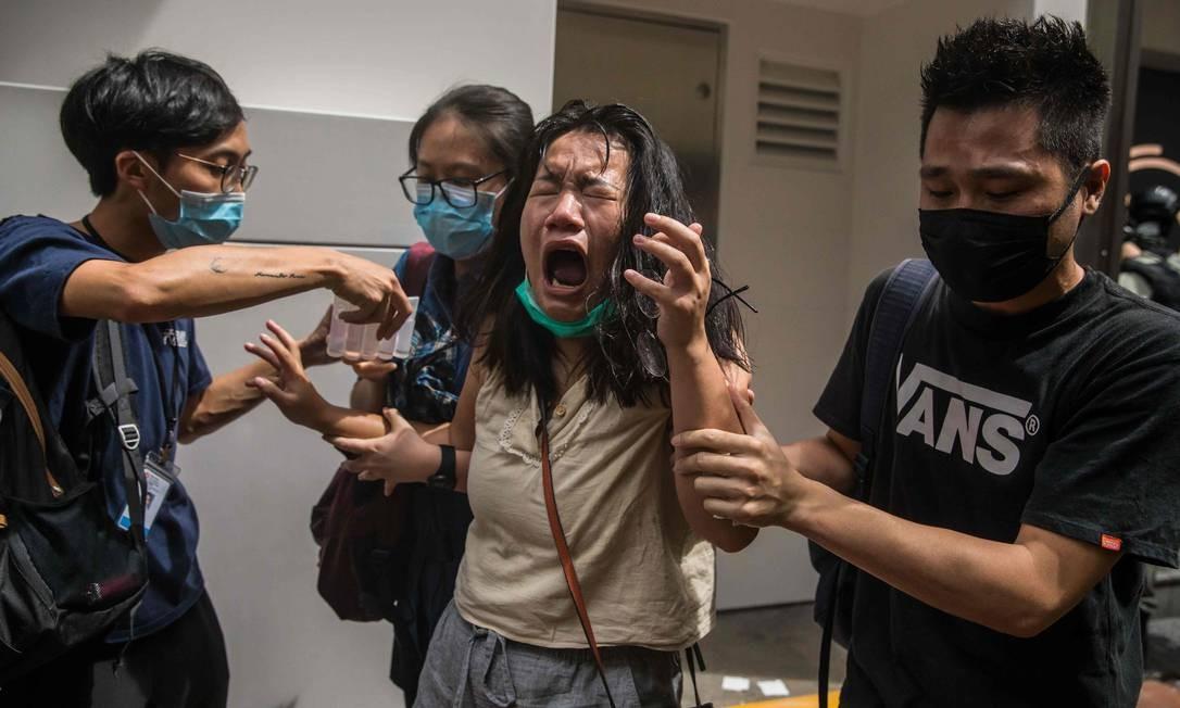 Mulher reage após ser atingida por spray de pimenta pela polícia, que dissipava manifestantes protestando contra a lei de segurança nacional em Hong Kong Foto: DALE DE LA REY / AFP